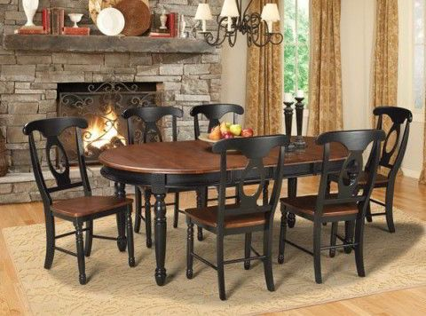 The British Isles Dining Set is a classic take on English country design. This traditional dining room table features an oval, cherry colored table top, with a black base and legs, accompanied by four side chairs.