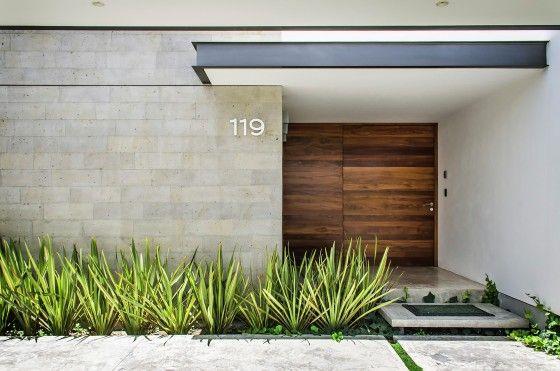 Vista del acceso principal a la casa jerarquizada con volado de techo y ancha puerta de madera | ADI Arquitectura