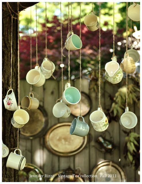 Tea cups hanging on teacup hooks in a piece of wood or something with bird food