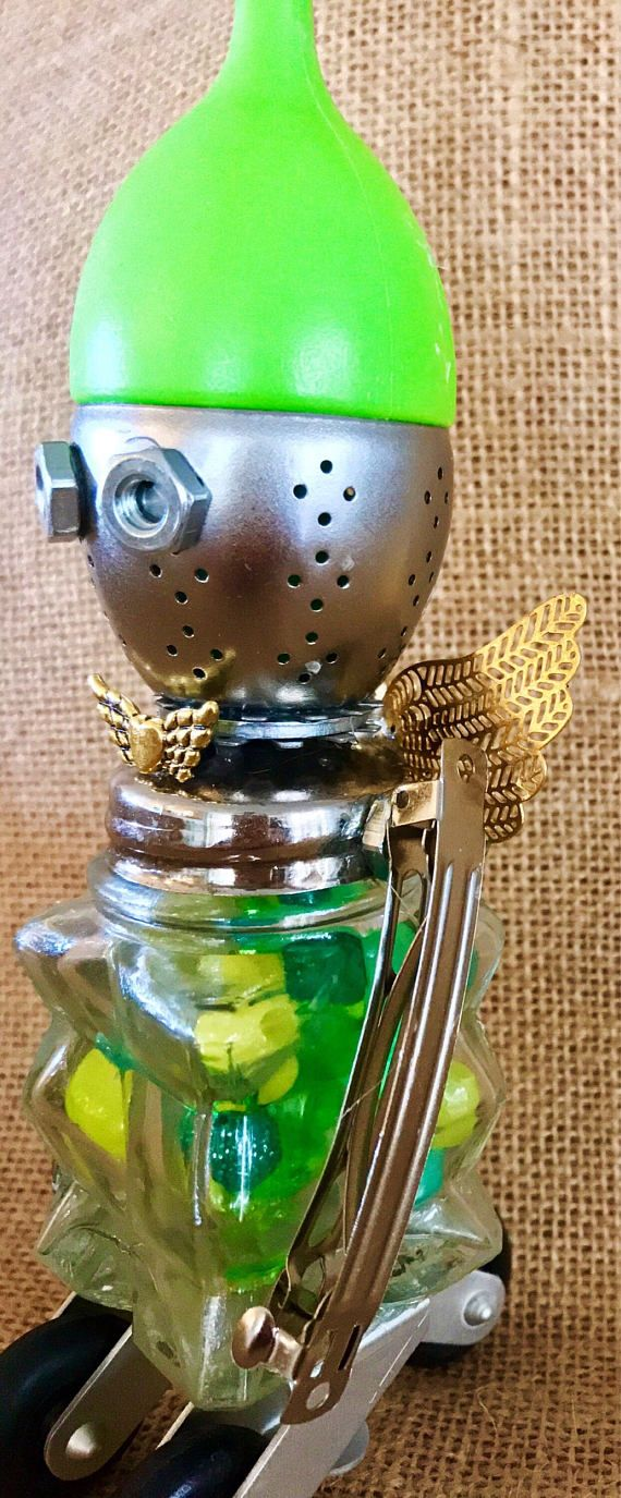 How cute is this little fella? Hes got a full tummy & is ready to roll out to meet his friends! Hes wearing his spring hat today! His life started out as a salt shaker, a tea strainer, random small wheels, metal barrettes, angel wings & random metal pieces He stands an adorable, 10 tall to the top of his hat.