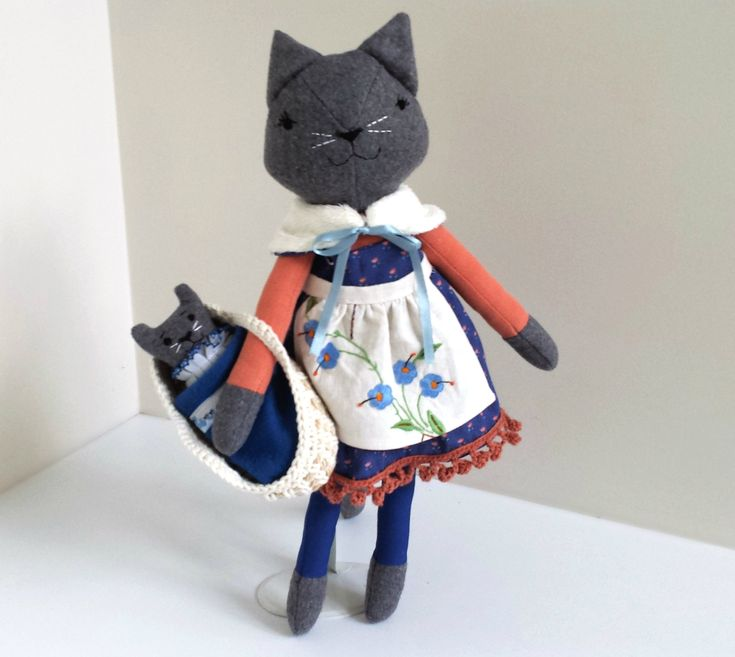 This cat doll is named Mabel.  She is a one of a kind, handmade doll and she has a kitten that likes to sleep in her Moses basket.Mabel measures approximately 46 cm (18 inches) tall from tip of her ears to toes.She wears a pretty blue dress with a handmade crochet lace trim, a reversible wrap and a vintage fabric apron. All removable.The kitten (approx. 6 inch), has a faux fur tail and comes with a Moses basket and blanket.Mable has buttons that secure her arms to her body...