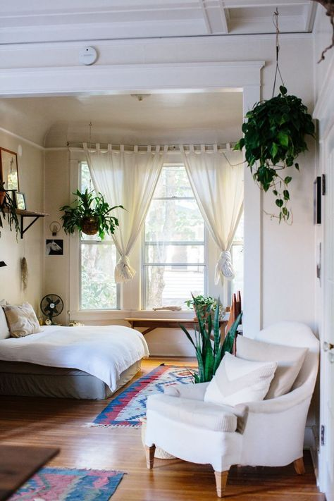 Hanging plants and colorful rug in the bedroom.