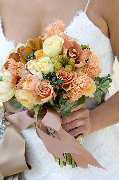 """Offset a simple gown with a bouquet full of color and texture, like this bouquet made of orange and yellow orchids, roses and craspedia. See the """"Personal Flowers"""" Photo Gallery"""