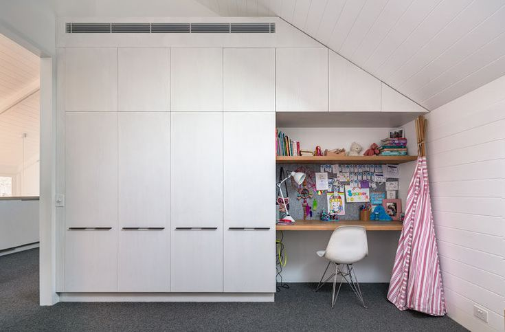 Custom built-in white cabinetry makes the most of the space, and a small desk is perfect for homework.