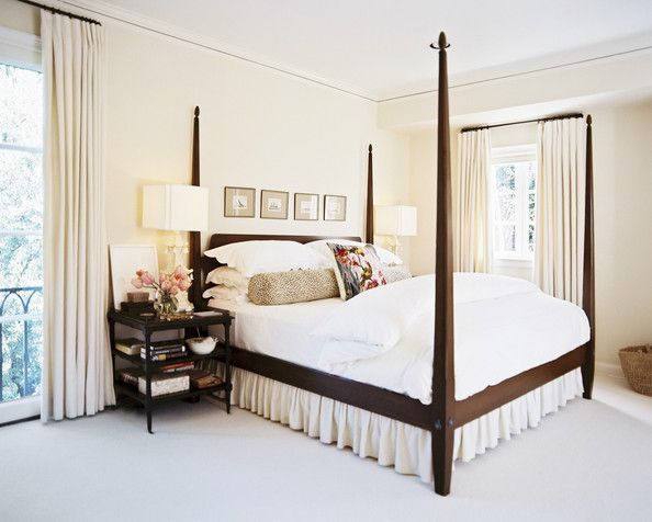 Hollywood Regency Bedroom  A wooden four-poster bed outfitted with white scalloped bed linens  Details: Beige-White Hollywood Regency Bedroom