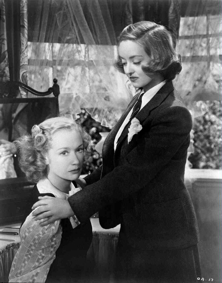 Old Acquaintance (1943), starring Bette Davis, Miriam Hopkins, and Gig Young.  Medium shot of seated Miriam Hopkins as Millie Drake and Bette Davis as Kit Marlowe.