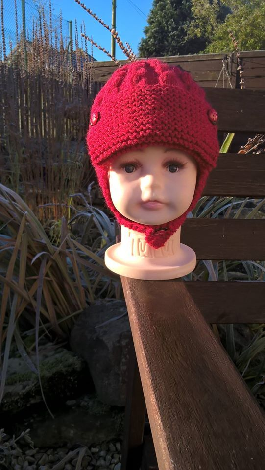 This red cable design aviator hat is to fit approximately 0-3 months (generously sized) and features little ladybird buttons. It's knitted in a baby wool and acrylic mix yarn, which is machine washable at a 30 degree delicate cycle. £7 + £3 P&P