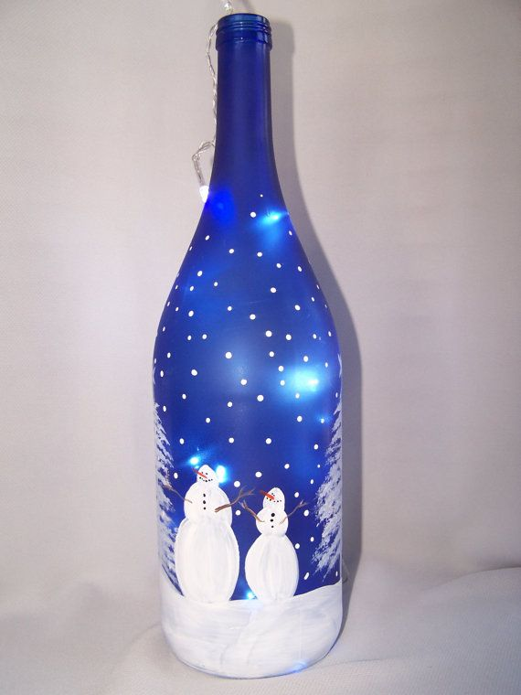A family of snowmen are enjoying the snowfall as they gather around the Christmas tree. Hand painted on a cobalt blue wine bottle and is
