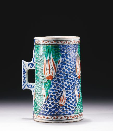 An Iznik polychrome pottery tankard, Turkey, circa 1575-80 of tall cylindrical form with applied with a square-form handle with projecting corners and elongated mounts, decorated in underglaze red, cobalt blue, green and black outline with a bold design of tulips rising on fields of fish-scale pattern, a frieze of interlocking keyfret design around the rim and base, the handle with cursive scrolls and hatching 20.8cm. height.
