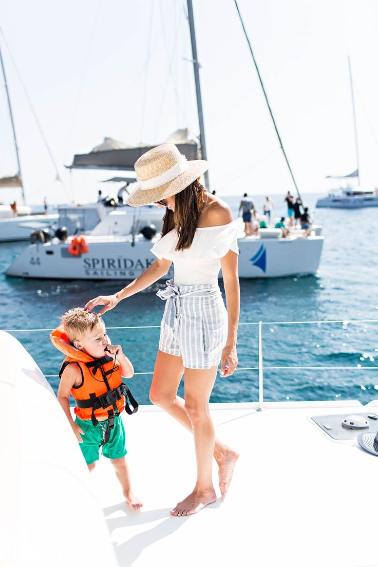 Santorini Sunset Sail in a white off the shoulder top and striped linen shorts