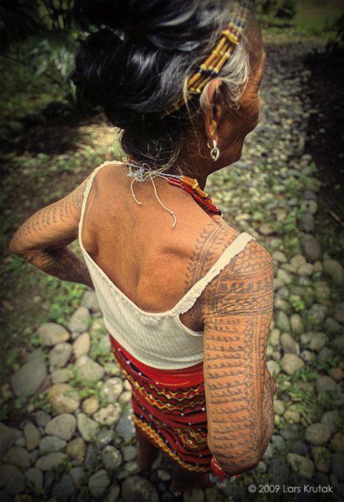 Beautiful fern design tattoos on the back of an elder Kalinga woman�s arm. A centipede crawls across her shoulder.