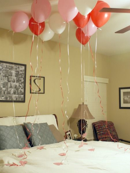 balloons over bed with notes of why you love him tied to the end for valentines day