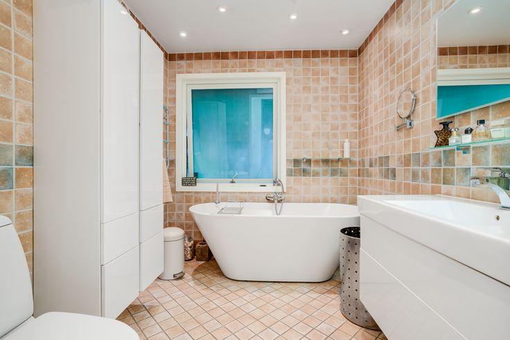 fint badrum i jordnära, varma färger och med läckert badkar