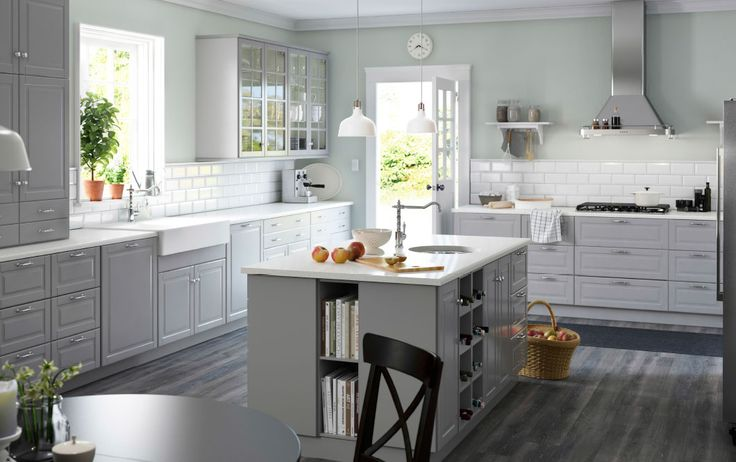 A large grey country kitchen with a lot of drawers, wall cabinets and a kitchen island.