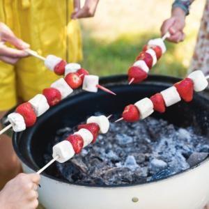 Geroosterde marshmallowspies met aardbei. Rijg de marshmallows en de aardbeien om en om aan de spiesen. Smelt de melkchocolade in een hittebestendige kom bove..