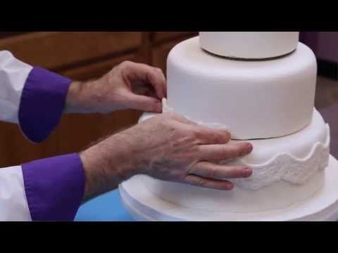Chef Alan Tetreault of Global Sugar Art shows you how to make your own fondant covered wedding cake. Learn how to cut, fill and ice the cake, cover with rolled fondant, assemble the three tiered cake, make molded borders and add flowers. This is Part 1 of the 2 part series.