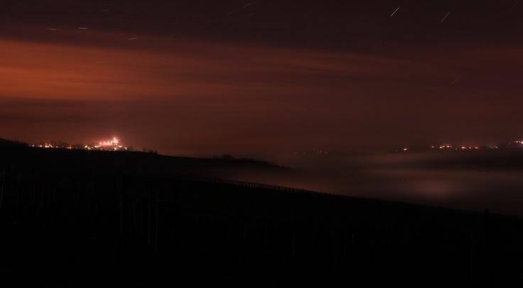 Nuvole di nebbia appaiono e scompaiono tra le colline dell'Oltrepò Pavese. Si vede il Castello di Mornico Losana visto da sudest.