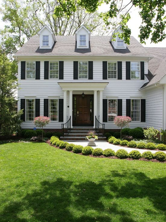 Beautiful dormers and shutters adorn this adorable colonial home. Especially love the lush landscaping!