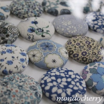 make fabric buttons out of favorite blue fabrics, line them symmetrically, and frame it.  Beautiful!!