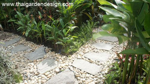 Garden path - Large flat flagstones surrounded on either side by large pebble stones and light coloured rocks
