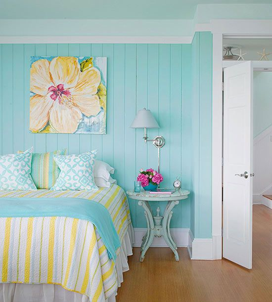 Use a favorite piece of art to inspire a bedroom's color scheme. Here, a powder blue and sunny yellow palette takes its cue from the tropical flower painting above the bed. Consider choosing a less dominate color from the art piece to be the starring color in your room. And if you're painting your walls a bright color, continue color on the ceiling in a hue that's a few shades lighter.