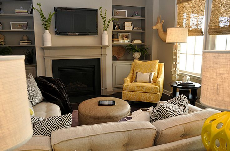 Super chic small living space with Kenneth Wingard Yellow Truffault Lamps, oatmeal linen sectional sofa, mushroom linen round storage ottoman, taupe built-ins flanking TV and taupe fireplace, yellow curvy accent chair, Crate & Barrel Union Side Table, horn cube floor lamp and black & white greek key pillows.