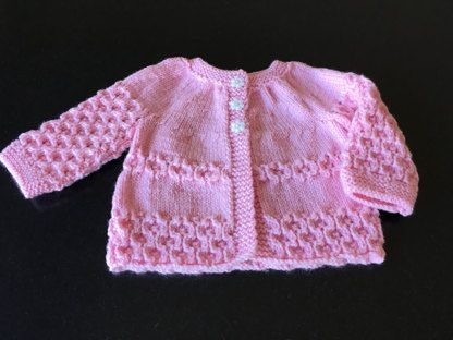 This sweet little jacket is knitted from the bottom up, and the sleeves are worked flat then joined to the yoke. This means minimal seaming, and is perfect for dressing up any outfit. Would certainly dress up baby's Christening outfit if knitted in traditional white.