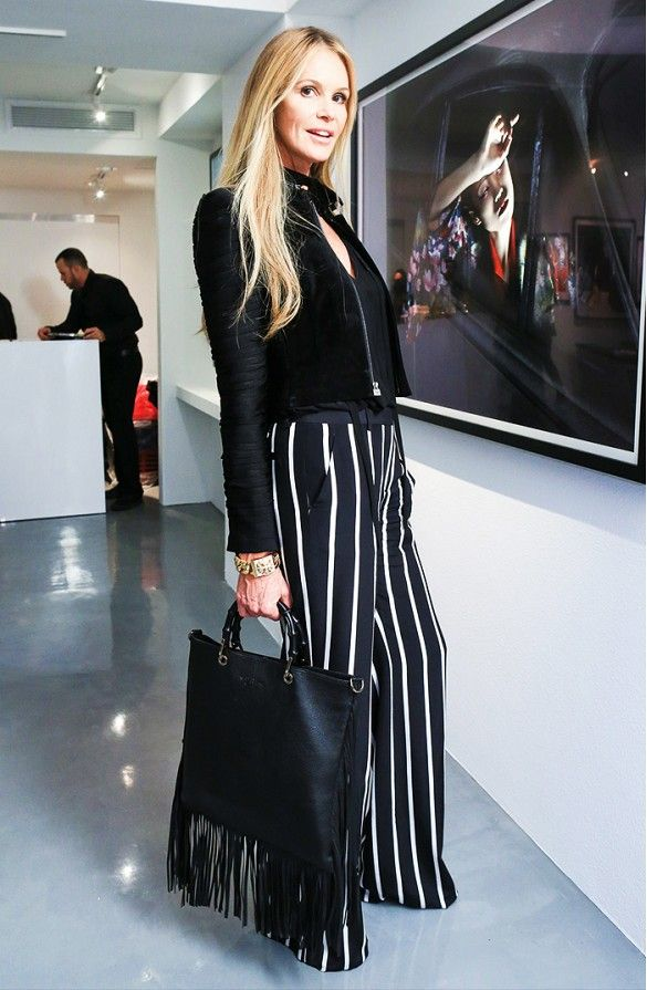 elle macpherson in a cropped jacket, striped wide-leg pants and a fringe bag