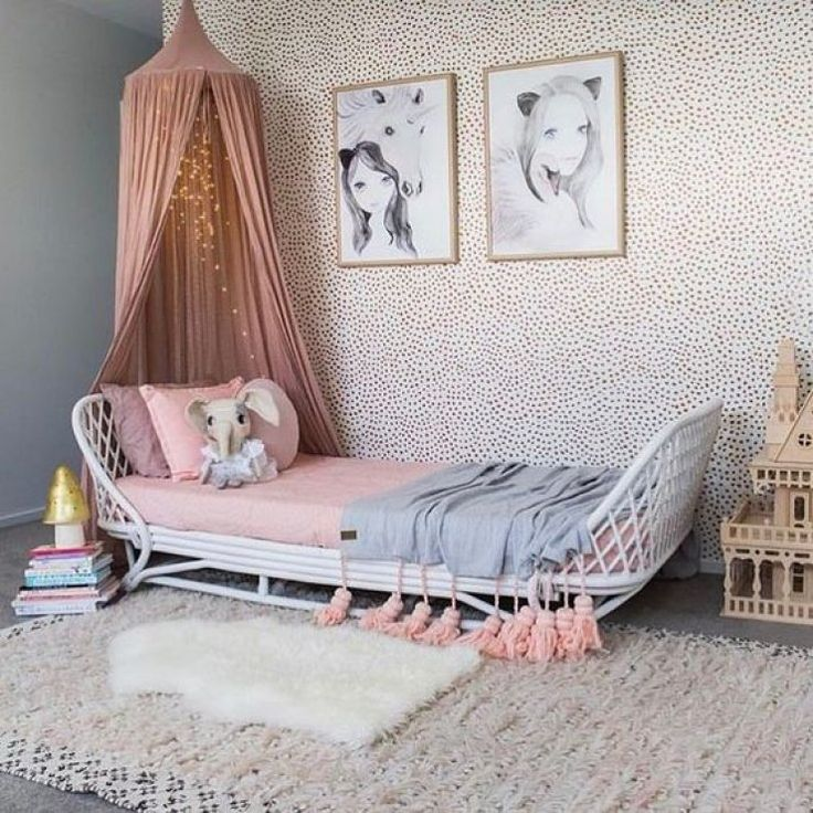 Girl's boho bedroom design featuring a rattan bed, pink hanging canopy, and dot patterned wallpaper on an accent wall - Children's Room Ideas & Decor .