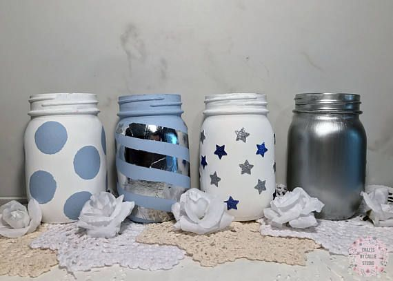Four 16 oz. Kerr mason jars hand painted in blue and white chalkboard paint and metallic silver paint. These mason jars are perfect for baby showers for boys. Im actually using similar ones for my baby shower in May. I cant decide if I should use them as centerpieces or silverware/straw/napkin holders. What do you think?!      Mason Jar Size (individual): 3 L x 3 W x 5.75 H      *Flowers and lids NOT INCLUDED.