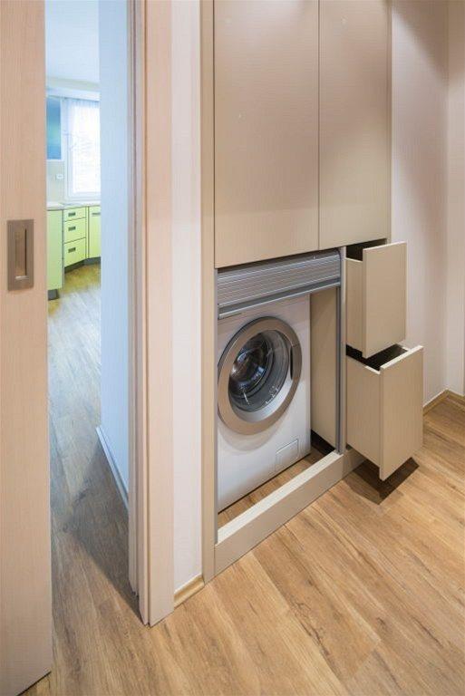 Veskříni, která vznikla v nice po bývalém vstupu do kuchyně, je skrytá pračka, vedle ní jsou zásuvky na špinavé prádlo. Pračku zakrývá roleta, která může být při praní otevřená.