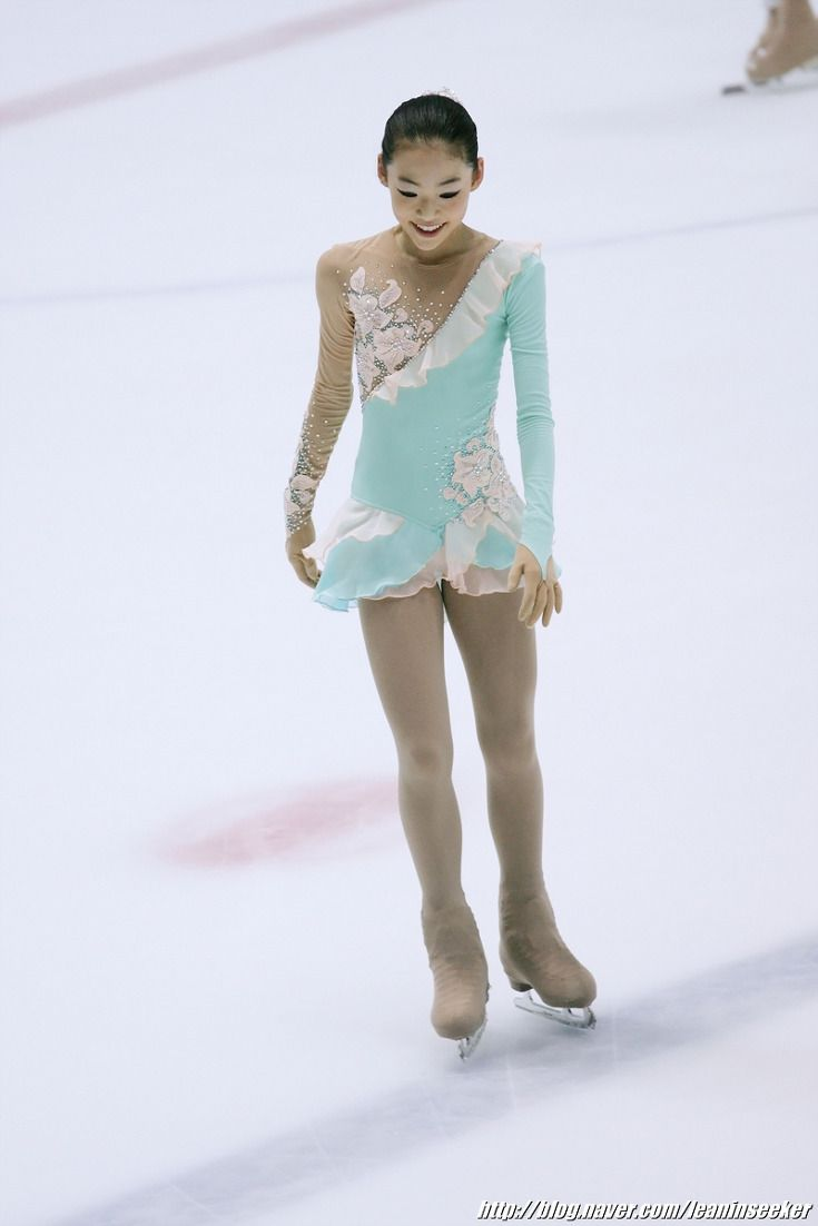 A figure skater's costume of mint color with decorative lace lining across from the shoulder to the other side of the chest accentuates beauty and loveliness. A little bit puffy skirt that diverts from the middle gives a little room for the waist/hipline to be revealed.