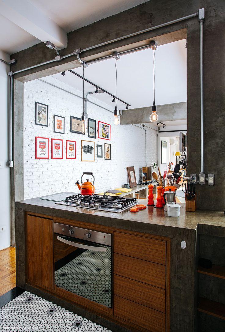 Cozinha integrada com estilo industrial tem piso com pastilhas em formato hexagonal e bancada de concreto.