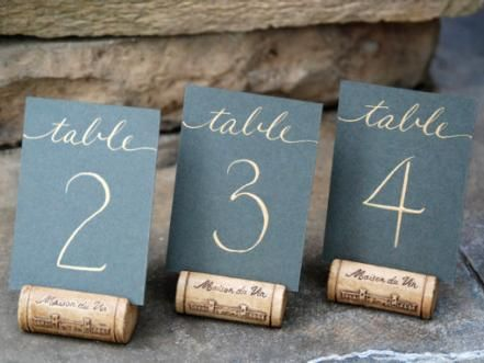 These+custom+calligraphy+table+numbers+add+a+simple,+yet+elegant+touch+to+a+table.+Using+a+wine+cork+as+a+stand+for+the+table+number+is+a+creative+and+inexpensive+way+to+add+sophistication+to+your+centerpiece.+Design+by+Jane+Dolan+of+Southern+Calligraphy.