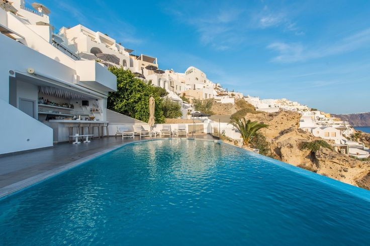 Enjoy a drink with a view of Santorini at Santorini Secret Suites and Spa's pool bar