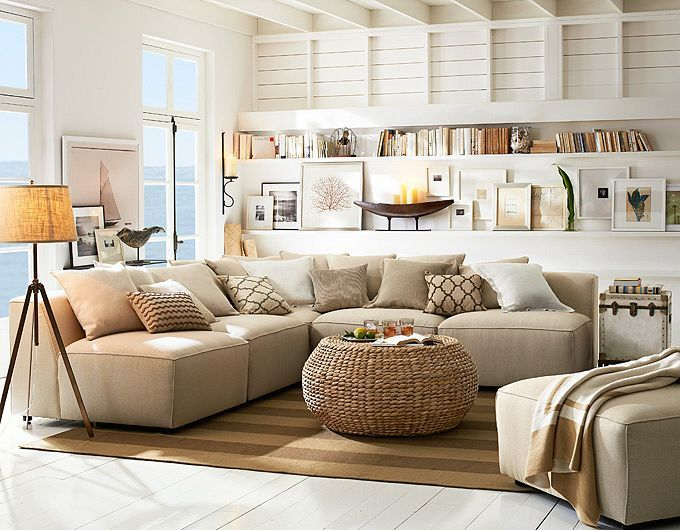 Another home run!  A white washed room of high ceilings, exposed beams, and French doors are the perfect canvas to layer this gorgeous room upon.  Love the frames artfully, with seemingly hap-hazard placement, leaning on the open shelves. The tri-pod lamp and  nautical touches reinforce this room's casual  chic.  Pottery Barn.
