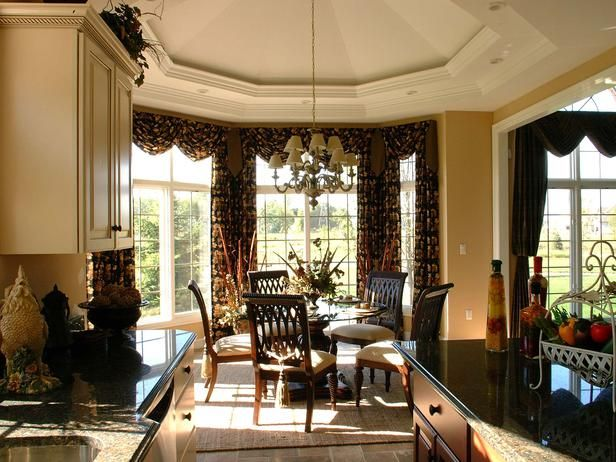 A mix of traditional furnishings and architectural elements presents visual interest and charm in this traditional breakfast nook. Long drapery panels between the windows provide the illusion of a vast wall of windows.
