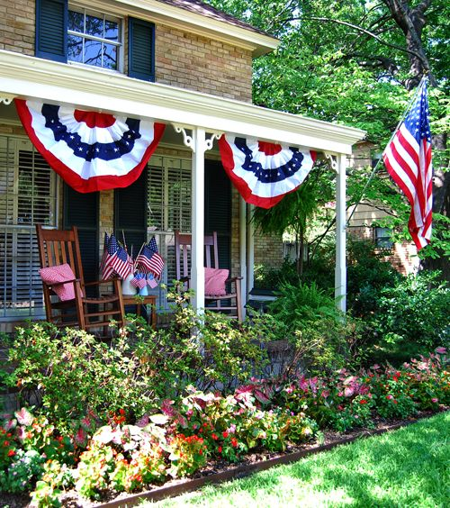 this home has beautiful tropical foliage landscaping with a front porch outfitted for 4th of july american flag