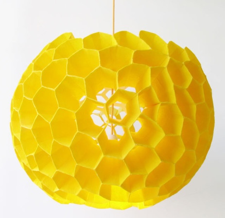 Honeycomb light in orange or white hanging in open staircase.