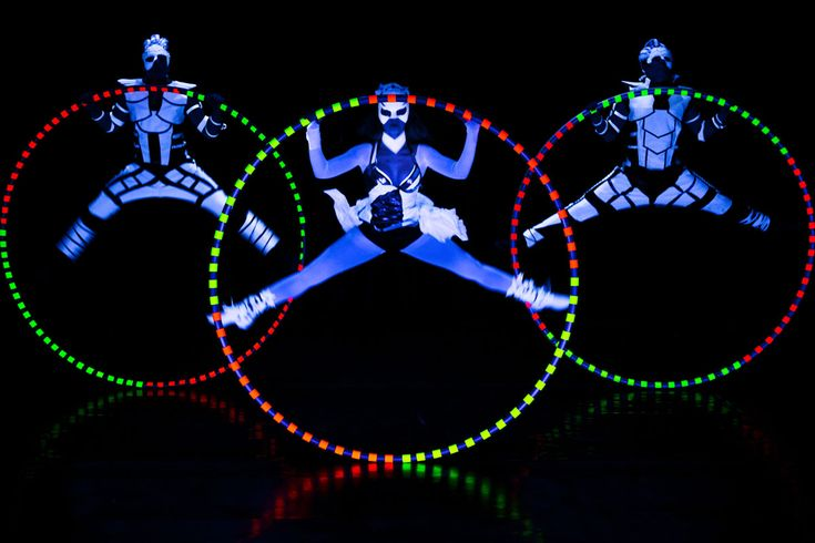 Three performers with three Cyr Wheels in black light show Crystal Light- Anta Agni. http://antaagni.com/crystal-light-show/