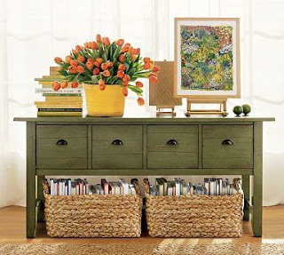 low green cabinet, vignette of books, flowers in pot, framed art on easel, storage basket with books and magazines under cabinet