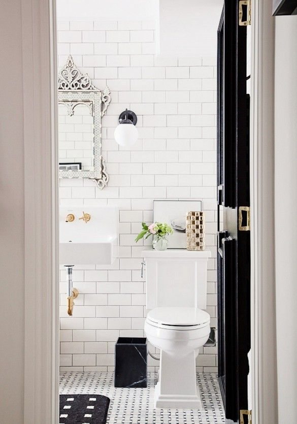 White subway tile in bathroom with black door, mirror above sink, and small flowers