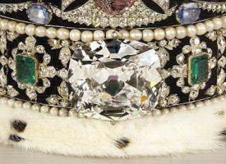 """Corona Imperial de Estado: Cullinan II. Diamante de 317.40 quilates, 2ª pieza más grande obtenida tras tallar el diamante Cullinan (""""la Estrella de África""""), el más grande del mundo, hallado en 1905 en una mina sudafricana. Propiedad de Sir Thomas Cullinan que regalaría el diamante en bruto al Rey Eduardo VII, quien ordenó tallarlo en 1906, obteniéndose 150 piedras talladas. El Cullinan II fue colocado en la corona en 1908, sustituyendo al Gran Zafiro que sería situado en la parte posterior."""