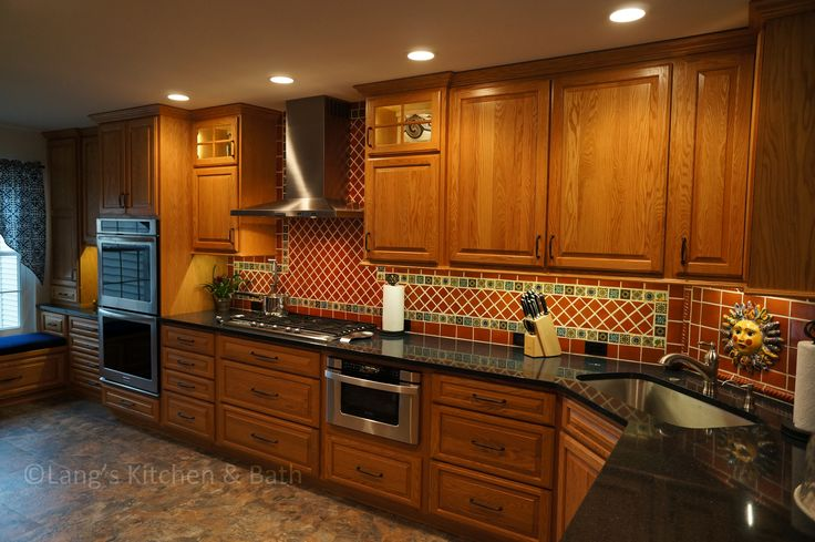 This kitchen renovation brings a taste of the southwest to the Jamison, PA home.  The distinctive design and color scheme is brought to life by the beautiful handmade terracotta tiles, which is complemented by the warm wood tones of the kitchen cabinets.  Extra features like a dish drawer cabinet, countertop pot filler, built in laundry center, and chimney hood add to both the style and practical elements of the kitchen.