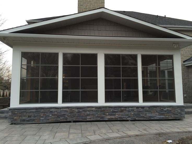 Exterior of a sunroom built by The Anything Guys. Stone and vinyl siding.