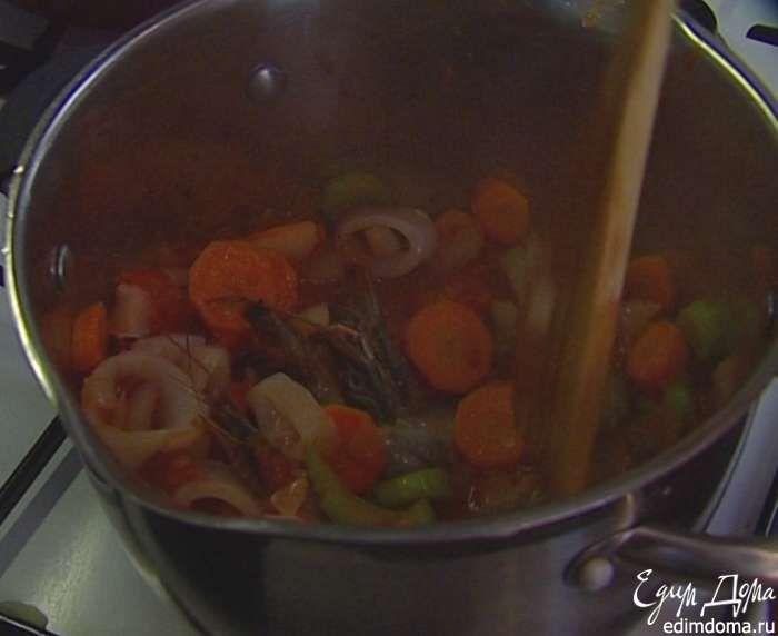 Отправить в кастрюлю с овощами полбанки помидоров вместе с соком, креветки, кальмары и тушить еще несколько минут.