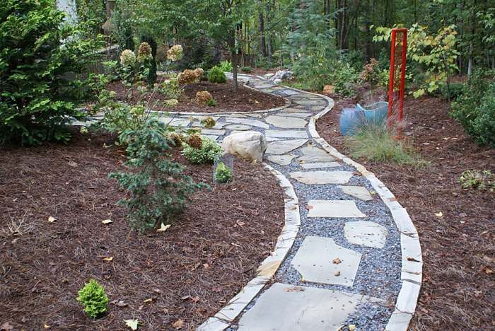 Weaving narrow walkways of flagstone are bedded in crushed rock. The natural stone border is used to keep the gravel walkway materials from migrating into the pine beds. Picture compliments of www.nichegardenslandscaping.com