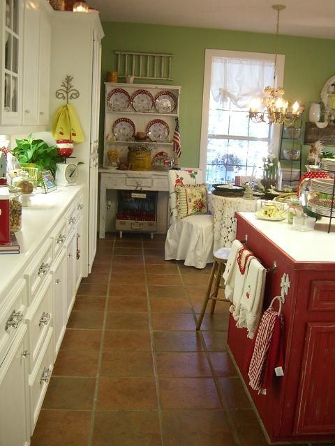 This is Tina's sister Kathy's cottage kitchen. I love the light green walls and creamy white cabinets with dark cherry red color accessories.