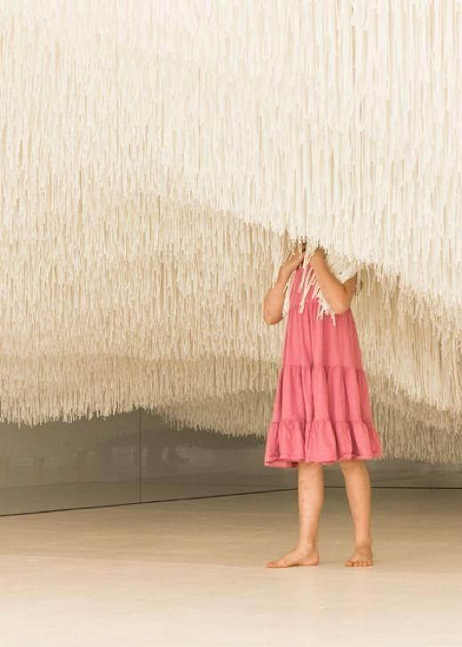 """""""liminal air"""" is an installation of approximately 123,000 white threads in the queensland art gallery. each strand varies in length and hangs from the ceiling, creating a cloud-like entity, which can be crossed by the visitors. shinji ohmaki."""