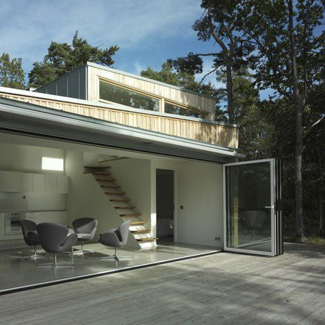 Large folding doors open this woodland house outside Stockholm onto a decked terrace that is shaded by a folding fabric canopy. The house by Swedish studio Schlyter/Gezelius Arkitektkontor is entirely clad in larch, milled into striped patterns by local carpenters. Inside the pine-framed building, walls are lined with stucco and have rounded corners. A timber staircase
